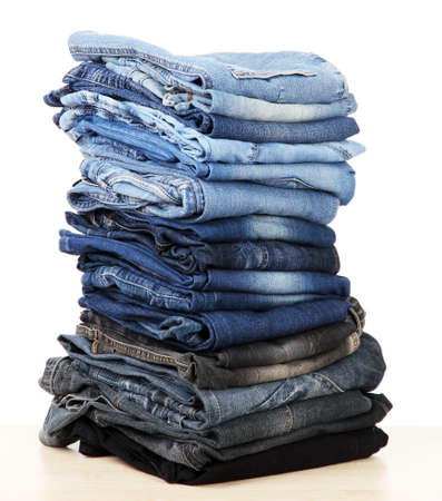 slacks: Many jeans stacked in a pile isolated on white