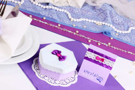 Serving fabulous wedding table in purple color on white fabric background photo