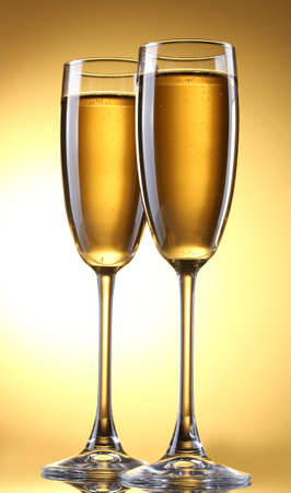 glasses of champagne on yellow background photo