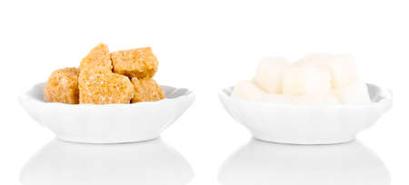 unrefined: Brown and white sugar cubes in saucers isolated on white