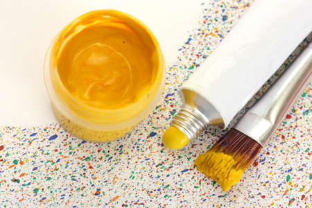 brushes with colorful paint, tube with watercolor and jar with gouache on colorful splashes background close-up photo