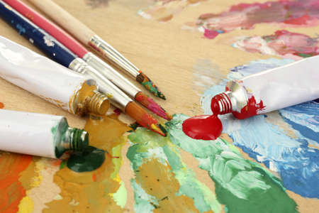 Abstract acrylic paint, paint tubes and brushes on wooden  palette photo