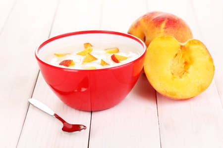Yogurt with peach in bowl on wooden background photo