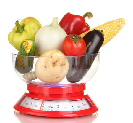 ripe fresh vegetables in the kitchen scales isolated on white photo