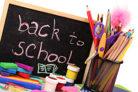 The words Back to School written in chalk on the small school desk with various school supplies close-up isolated on white photo