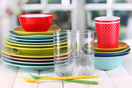 Colorful tableware on wooden table on window background photo