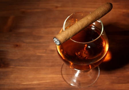 glass of brandy and cigar on wooden table photo