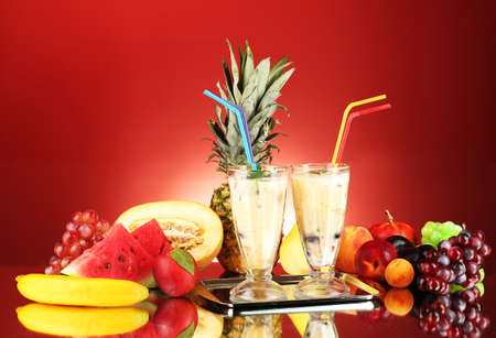 Milk shakes with fruit on red background close-up photo