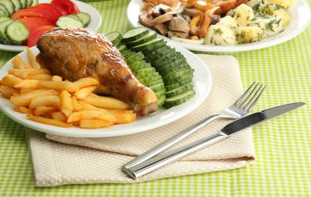 Roast chicken with french fries and  vegetables, on green table cloth photo