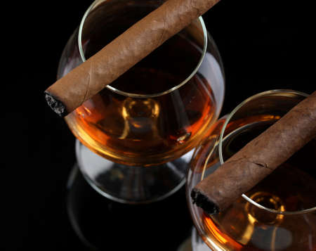 brandy: two glasses of brandy and cigars on black background