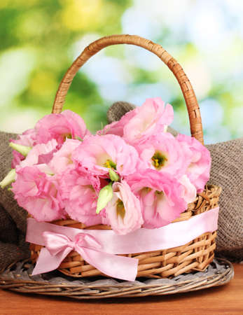 bouquet of eustoma flowers in basket, on wooden table, on green background photo