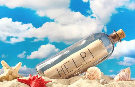 Glazen fles met notitie aan de binnenkant op zand, op blauwe hemel achtergrond