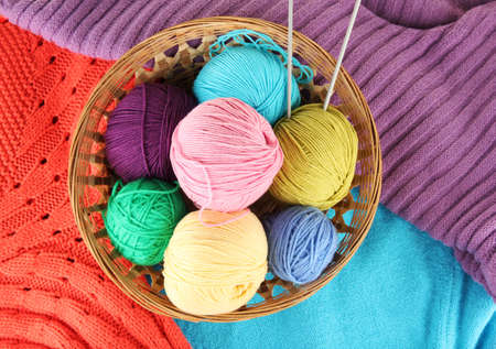 colorful wool sweaters and balls of wool close-up photo