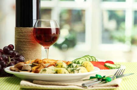 Roast chicken cutlet with boiled potatoes and cucumbers, glass of wine on green table cloth in cafe interior photo