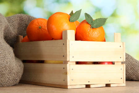 wooden box: Ripe tasty tangerines with leaves in wooden box on table on green background