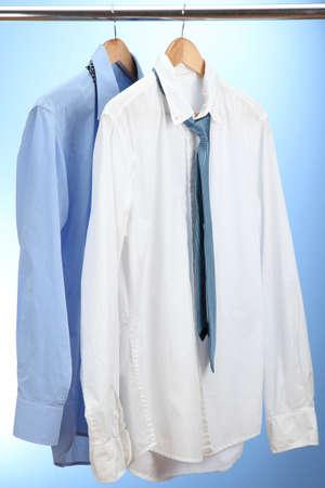 camisas: camisetas azules y blancas con el lazo en percha de madera sobre fondo azul