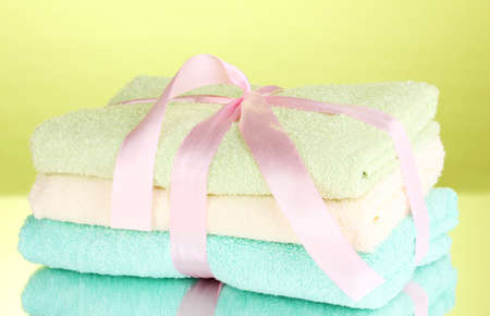 Colorful towels with ribbon on green background photo