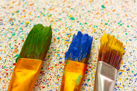 brushes with colorful paint on colorful splashes background close-up photo