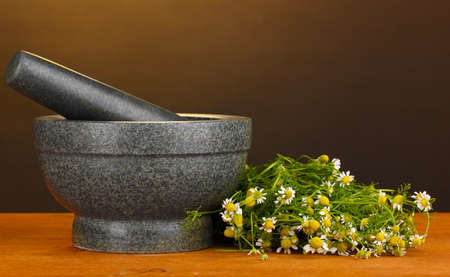 Chamomile flowers in mortar on wooden table on brown background photo