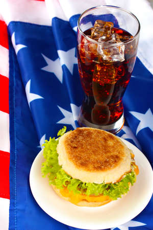 tasty sandwich and glass with cola, on american flag photo