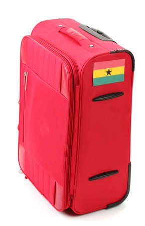 red suitcase with sticker with flag of Ghana isolated on white photo