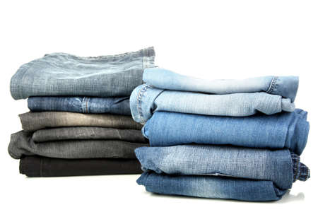 Two stacks of different jeans isolated on white photo