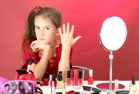 little girl in her mothers dress, is trying painting her nails photo