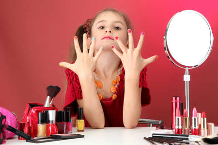 manicure salon: little girl in her mothers dress, is trying painting her nails