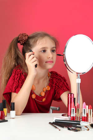 little girl in her mother's dress, is trying painting her eyelashes Stock Photo - 15741288