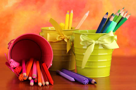 fine tip: Colorful pencils and felt-tip pens in pails on color background
