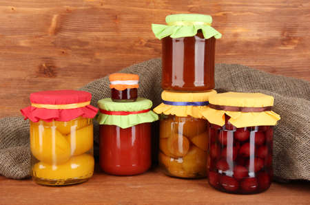 wooden lid: Jars with canned fruit on wooden background