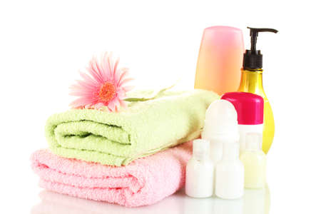 cosmetics bottles with towels and flower isolated on white photo