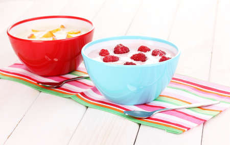 Yogurt with peaches and raspberries in bowls on wooden background photo