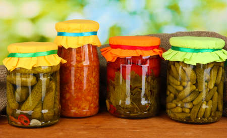 wooden lid: Jars with canned vegetables on green background close-up Stock Photo