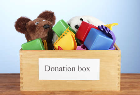soft toys: Donation box with children toys on blue background close-up Stock Photo