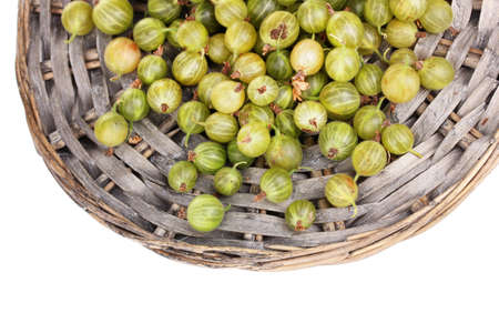 sweet segments: Green gooseberry on wicker mat isolated on white