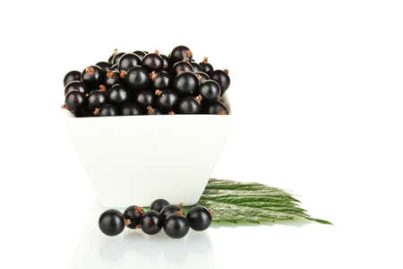 Fresh black currant in white bowl isolated on white photo