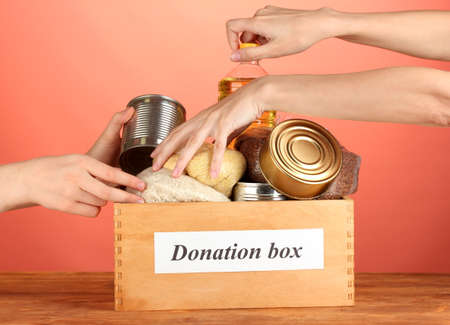 Donation box with food on red background close-up photo