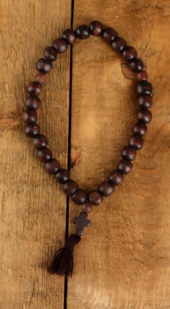 the Wooden rosary beads on wooden background close-up photo