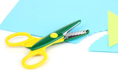 Colorful zigzag scissors with color paper isolated on white photo