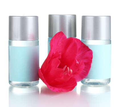 amenities: cosmetic bottles and flower, isolated on white