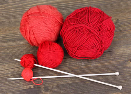 Red knittings yarns on wooden table close-up photo