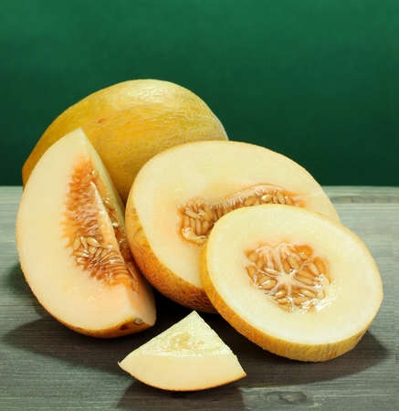 musk: Cut ripe melons on wooden table on green background