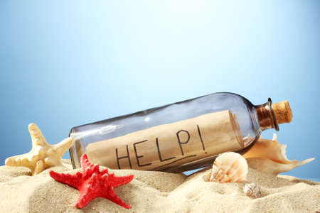 Glass bottle with note inside on sand, on blue background photo