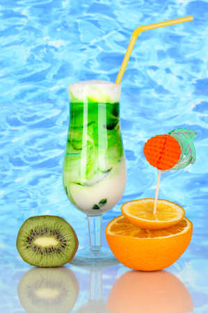 Delicious milk shake with fruit on blue sea background photo