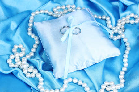 wedlock: Wedding rings on satin pillow on blue cloth background