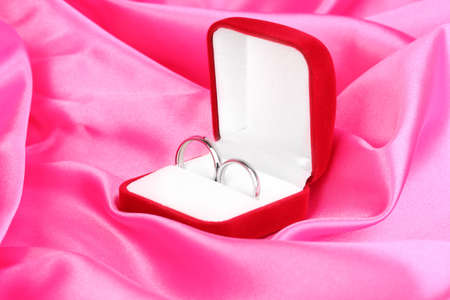 Wedding rings in red box on pink cloth background photo