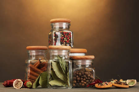 jars and spoons with spices on wooden table on brown background photo