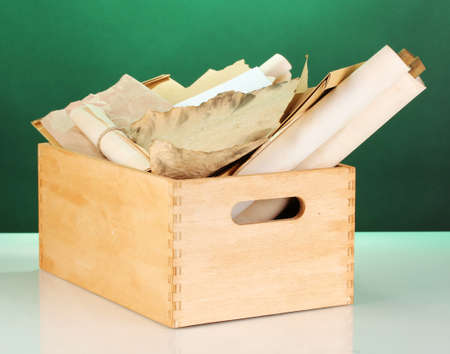 Wooden crate with papers and letters on green background photo