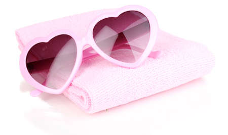 Pink heart-shaped sunglasses on towel isolated on white Stock Photo - 15104458